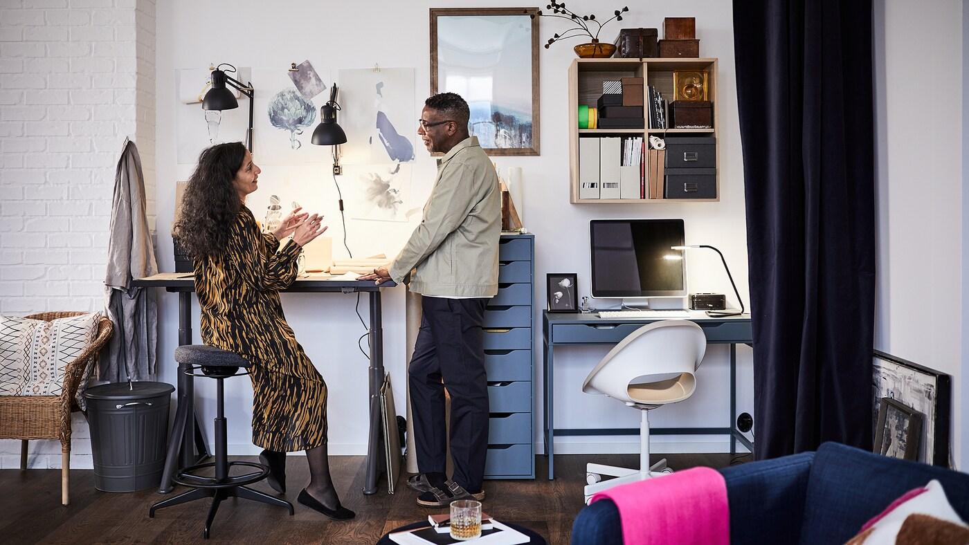Un homme et une femme dans un bureau à domicile. Lui se tient à côté d'un bureau assis/debout IDÅSEN, elle est assise sur un tabouret assis/debout LIDKULLEN.
