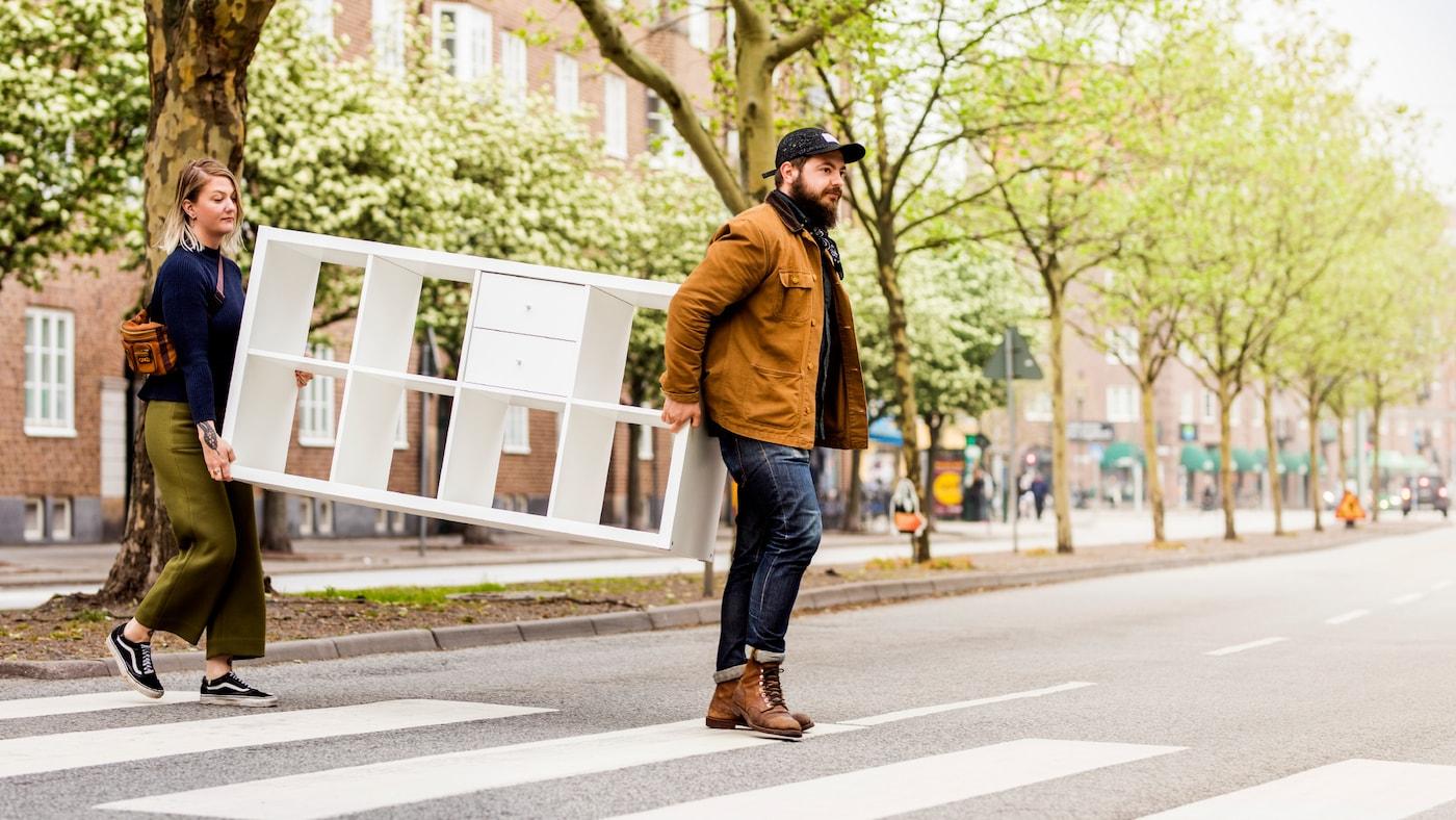 Un homme et une femme portant un meuble IKEA KALLAX blanc traversent la rue.