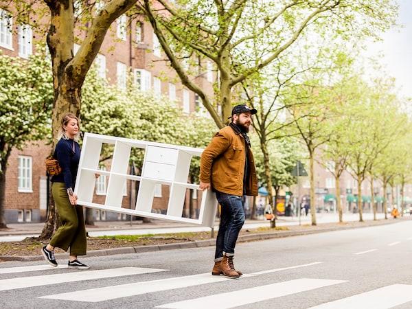 Un homme et une femme traversent une rue bordée d'arbres en transportant un rangement KALLAX blanc.