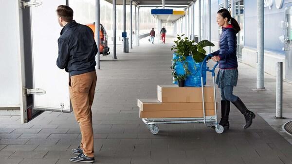 Un homme ouvre la porte d'une camionnette devant un magasin IKEA, une femme sort du magasin IKEA avec un camion à plateau rempli de paquets de meubles.