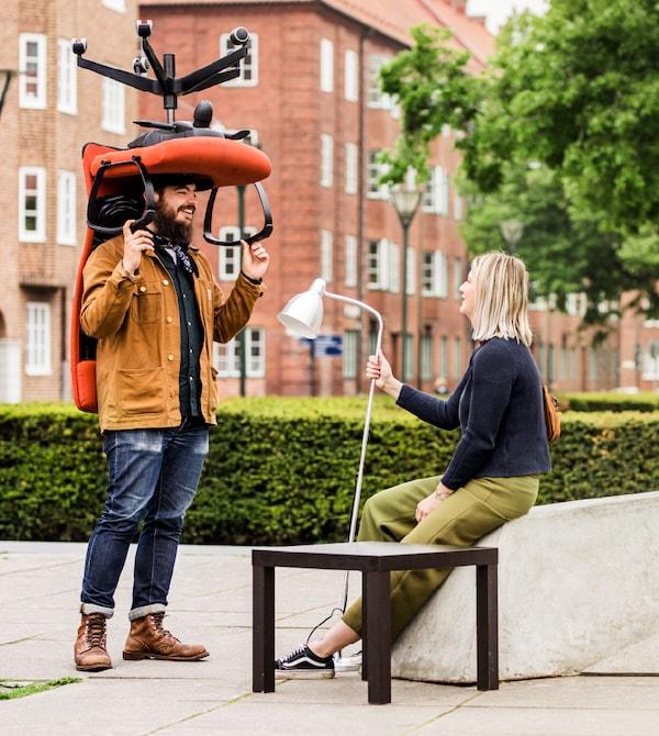 un homme portant un fauteuil de bureau et une femme assise tenant un lampadaire
