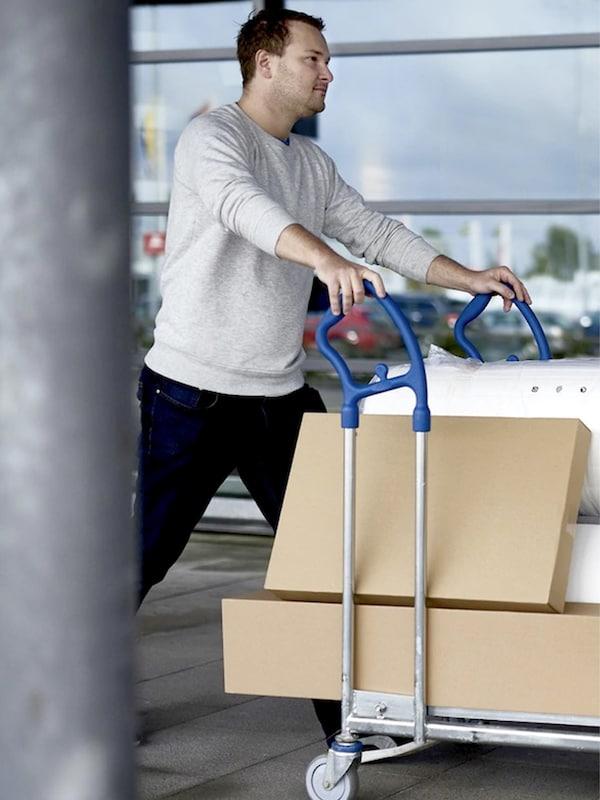 Un homme pousse un chariot avec une montagne de sacs plats sous la galerie d'IKEA, devant les fenêtres.
