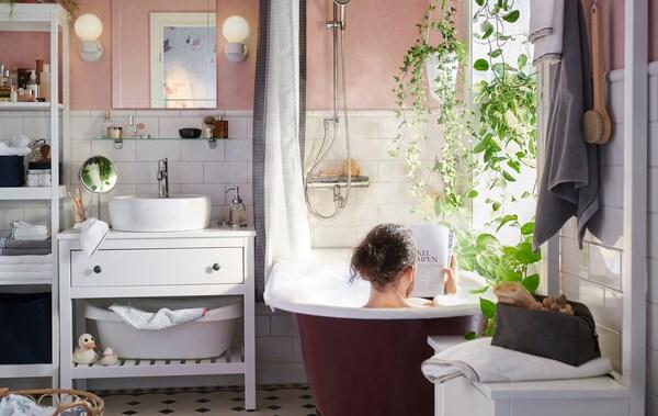 Un homme prend son bain dans une salle de bain aux murs rose pâle, aux carrelages et meuble lavabo blancs et décorée de plantes vertes.