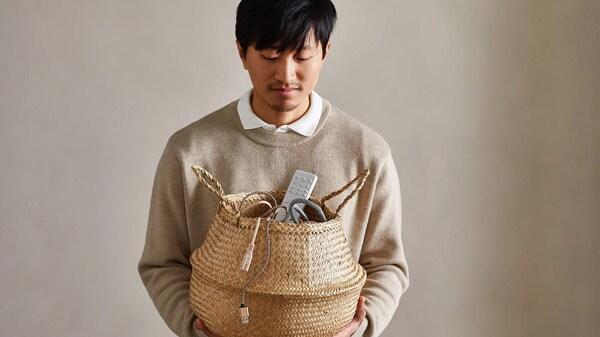 Un homme qui montre ses achats dans un panier en osier FLÅDIS