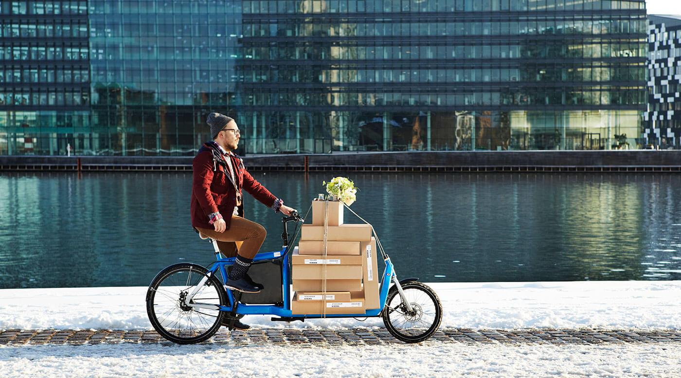 Un homme sur un vélo livrant des boîtes IKEA