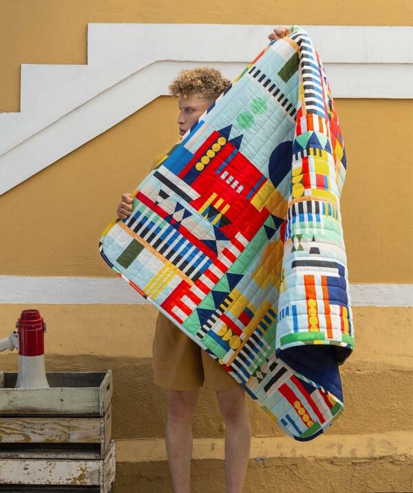Un homme tenant une couverture aux motifs multicolores devant un mur jaune.