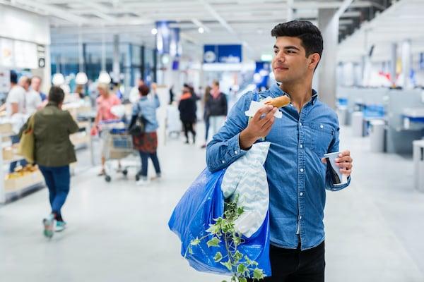 Un homme tient un hotdog et un sac bleu IKEA dans ses mains.