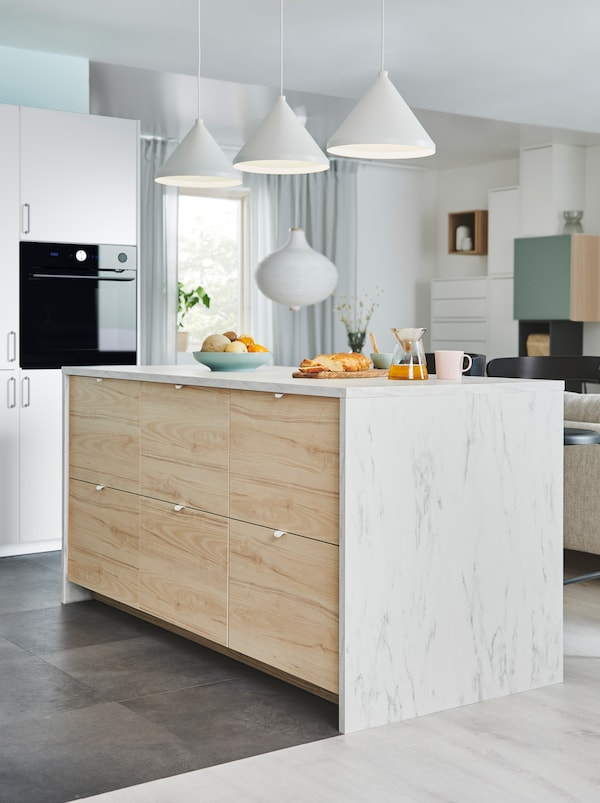 Un îlot de cuisine avec un côté composé de grandes façades de tiroir ASKERSUND, dans l'espace cuisine d'une pièce à aire ouverte.
