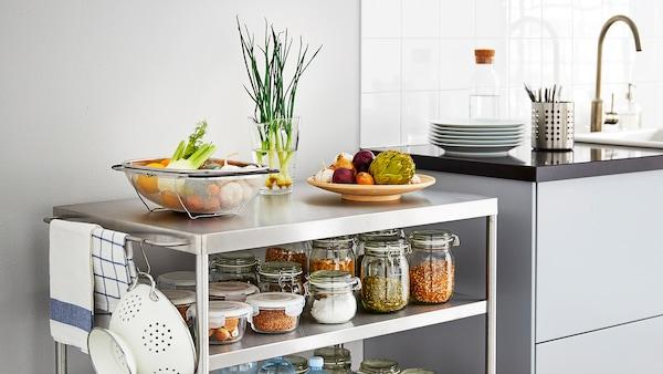 Un îlot de cuisine en métal avec les roulettes verrouillées et des ingrédients dans des bocaux près d'un comptoir de cuisine.