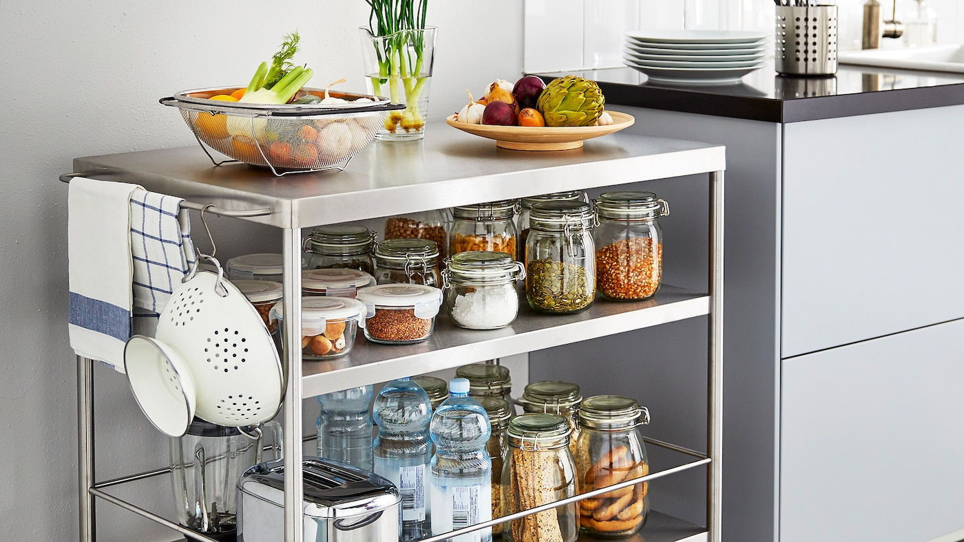 Un îlot de cuisine en métal sur roulette pour ranger des ingrédients en conserves, à côté d'un comptoir de cuisine.