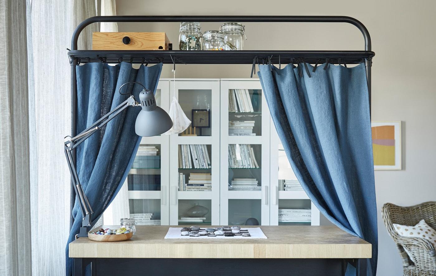 Un îlot de cuisine installé dans un séjour. Le support situé au-dessus, qui sert d'espace de rangement, est décoré de rideaux bleus.