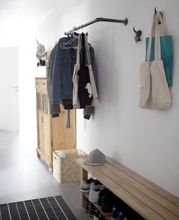 Un ingresso con una panca, un binario, ganci e un mobile – IKEA