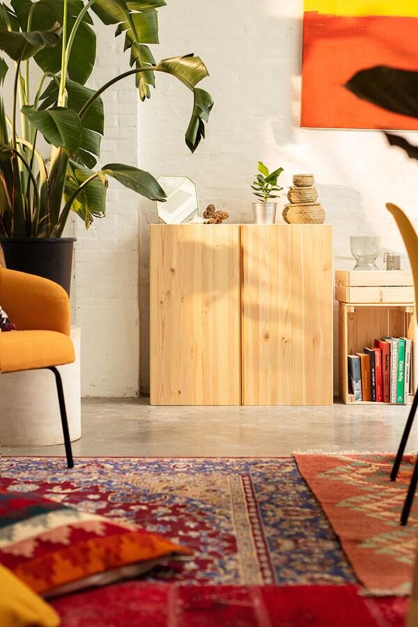 Un intérieur avec un placard en pin, un tapis oriental et des coussins et un grand palmier vert.