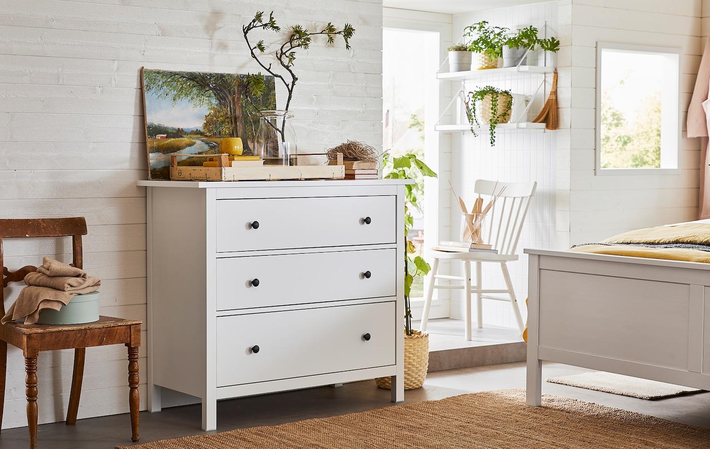 Un intérieur de chambre à coucher dominé par du bois et des plantes vertes, une commode à trois tiroirs à côté d'un pied de lit.