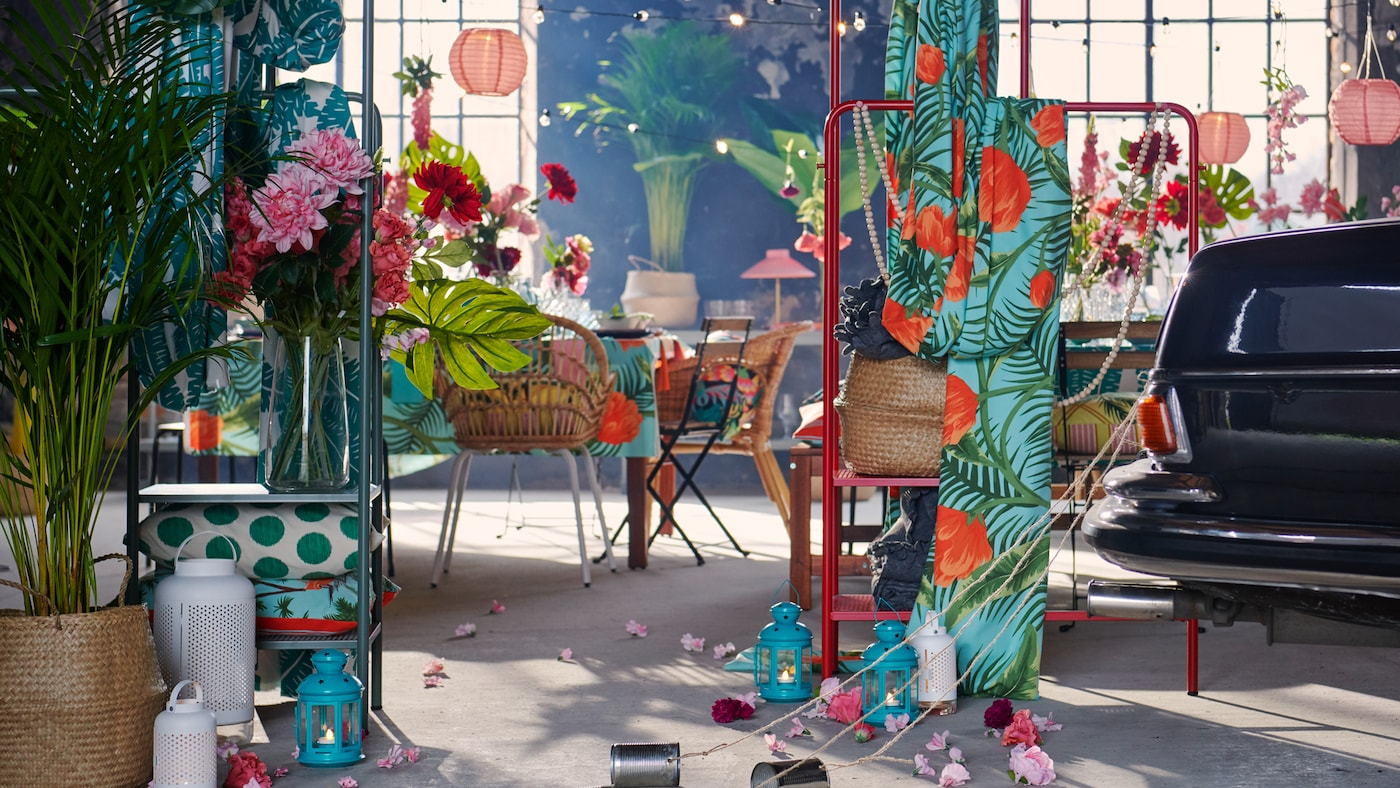 Un intérieur industriel spacieux préparé pour une fête avec des textiles, des décorations, des plantes et l'arrière d'une voiture avec des boîtes de conserve à la traîne.