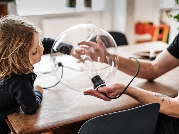 Un jeune enfant explore un luminaire en verre rond que tient sécuritairement un adulte.