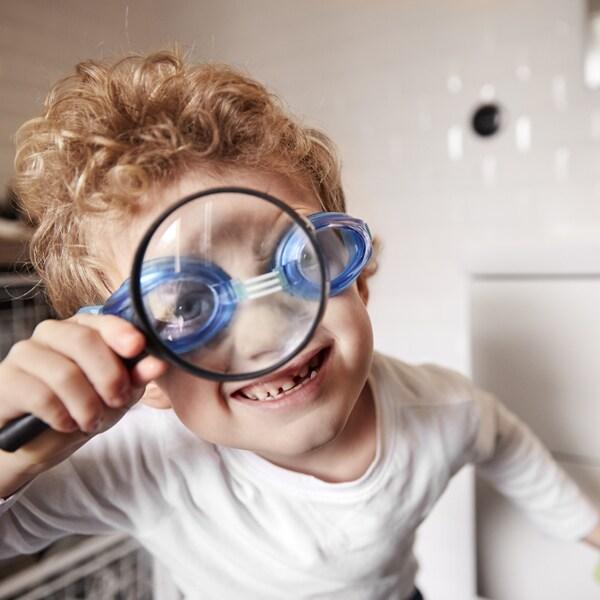 Un jeune garçon portant des lunettes de natation qui regarde dans une loupe en souriant.
