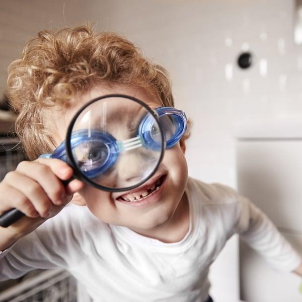 Un jeune garçon portant des lunettes de natation regardant à travers une loupe en souriant.