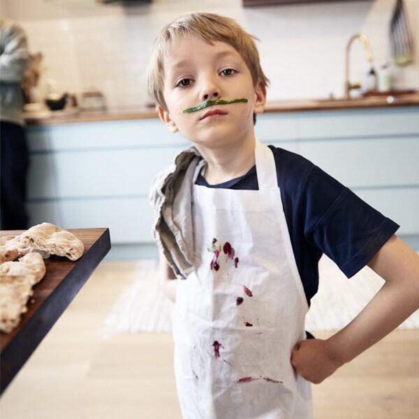 Un jeune garçon portant un tablier couvert de nourriture avec une fausse moustache dans la cuisine.