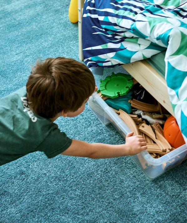 Un jeune garçon pousse une boîte de rangement transparente pleine de rails de petit train sous un lit orné de linge de lit coloré, sur un tapis turquoise.