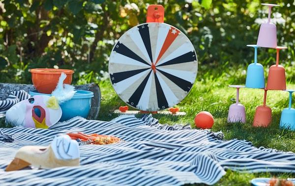 Un juego de la ruleta de la fortuna LUSTIGT en madera entre otros juegos y vajilla irrompible sobre una manta de pícnic.