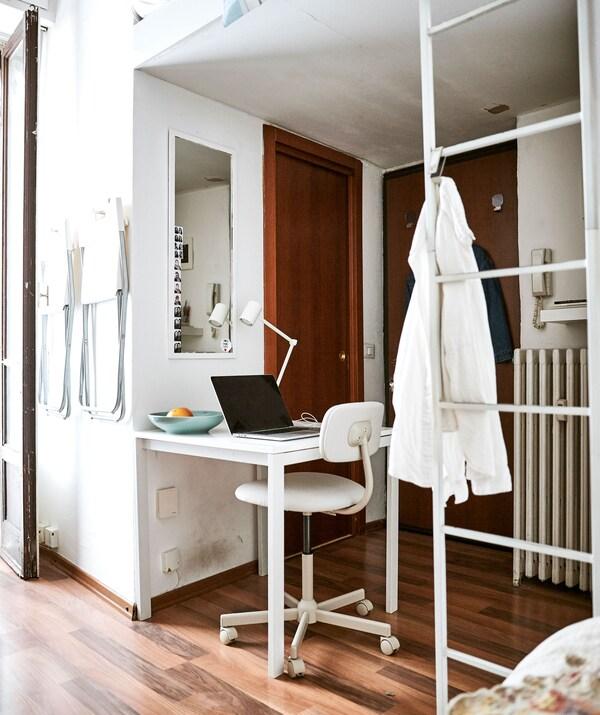 Un laptop pe birou, așezat în spațiul de sub patul său de la mezanin, cu o cămașă albă agățată de o scară albă.