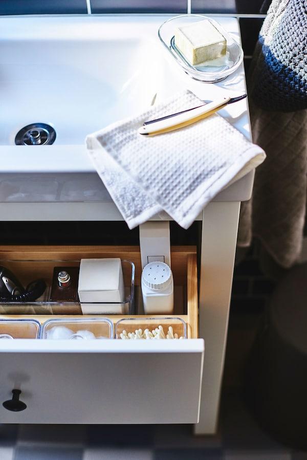 Un lavabo blanco de baño con un cajón abierto debajo.