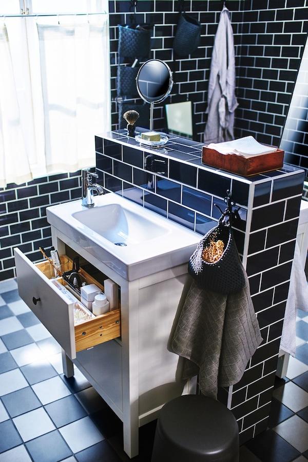 Un lavabo blanco en un cuarto de baño de azulejos negros, montado en una pared de media altura con otro lavabo al otro lado.