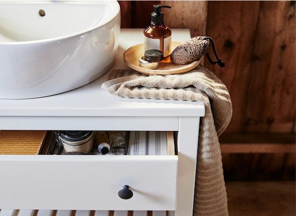 Un lavabo, un asciugamano e dei saponi su un mobile bianco con il cassetto aperto - IKEA