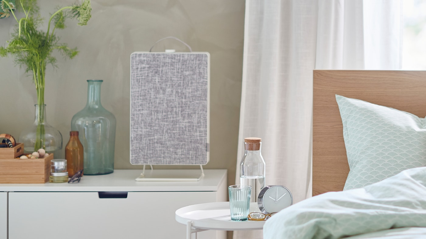 Un letto davanti a una finestra e un purificatore d'aria FÖRNUFTIG appoggiato sopra a una cassettiera.