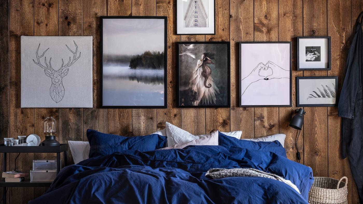 Un lit avec linge de lit bleu/blanc devant des murs en bois décorés de diverses images dans des tons de noir, blanc et gris.