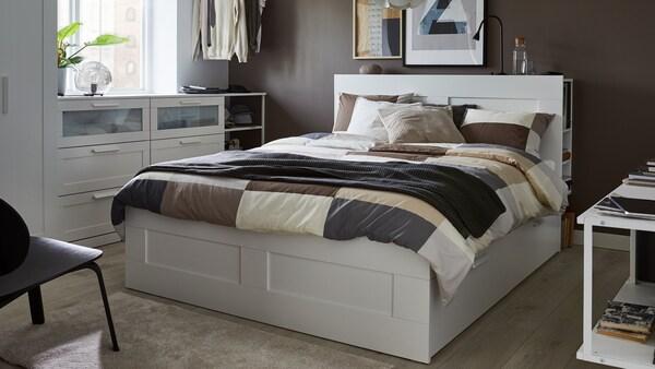Un lit blanc avec tête de lit blanche, housse de couette et taies d'oreiller à motifs bruns, plaid gris et coussins en blanc, gris et beige.