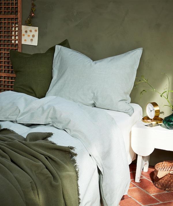 Un lit douillet avec de la literie blanche et verte, deux grands oreillers et des rayons de soleil provenant de la droite.