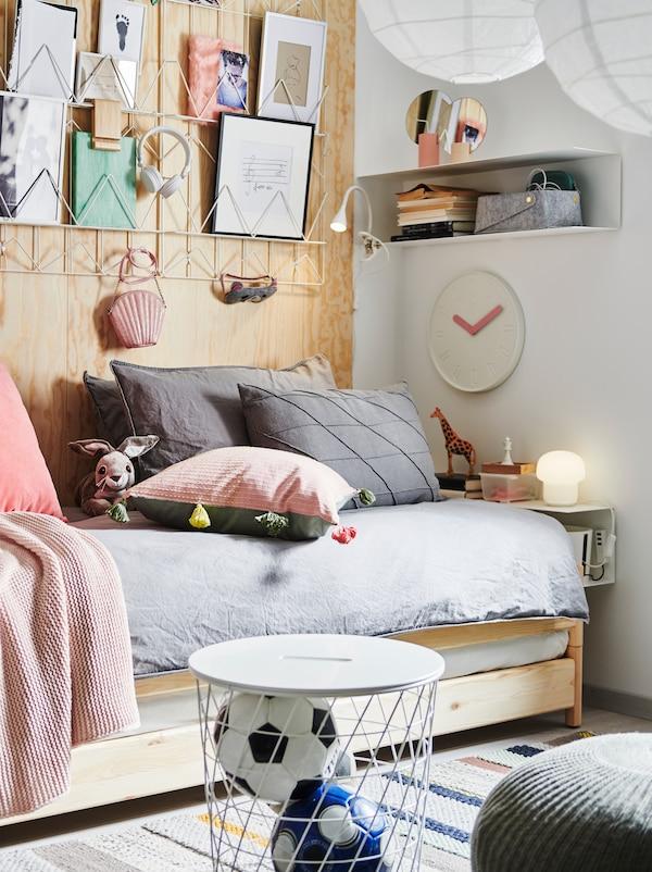 Un lit empilable UTÅKER sur lequel sont posés beaucoup de coussins, avec des créations en papier au-dessus, une étagère BOTKYRKA de chevet, un rangement et des décorations.