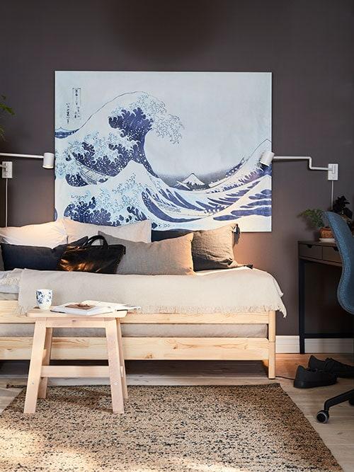 Un lit en pin et un tabouret en bouleau, avec un livre et une tasse devant, une grande peinture montrant une vague et deuxappliques.
