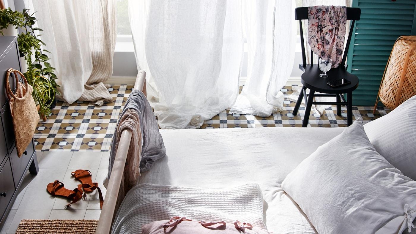 Un litGJÖRA et une chaiseNORRARYD noire sont disposés sur un sol carrelé devant une porte-fenêtre ouverte avec des rideaux blancs et beige.