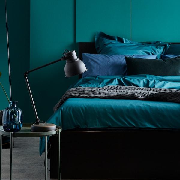 Un lit MALM avec de la literie, dont du linge de lit LUKTJASMIN vert foncé, repose contre un mur dans une chambre.