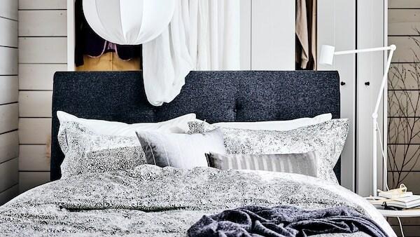 Un lit matelassé IDANÄS gris foncé avec une armoire-penderie blanche et un rideau blanc derrière et une suspension NYMÅNE au-dessus.