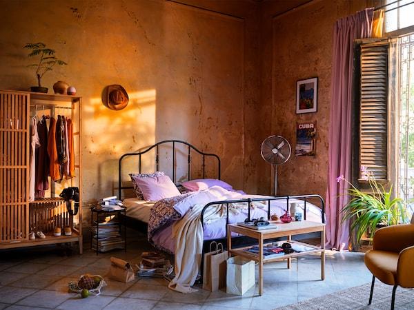 Un lit noir avec un cadre en acier et des détails couleur laiton. Le lit est placé contre un mur orange sur un sol carrelé.
