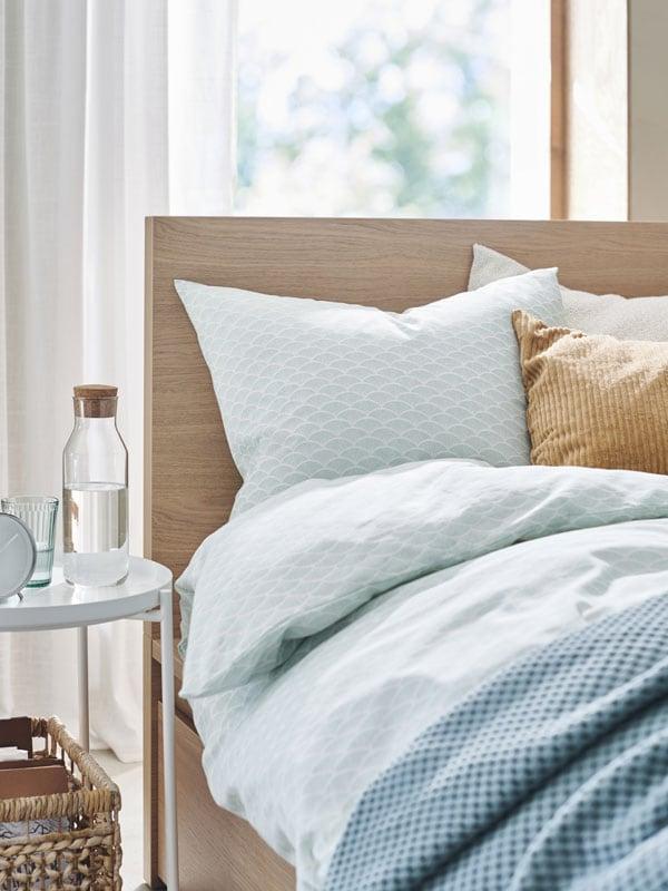 Un lit recouvert d'une housse de couette KASKADGRAN bleue. L'arrière-plan présente une scène ensoleillée.