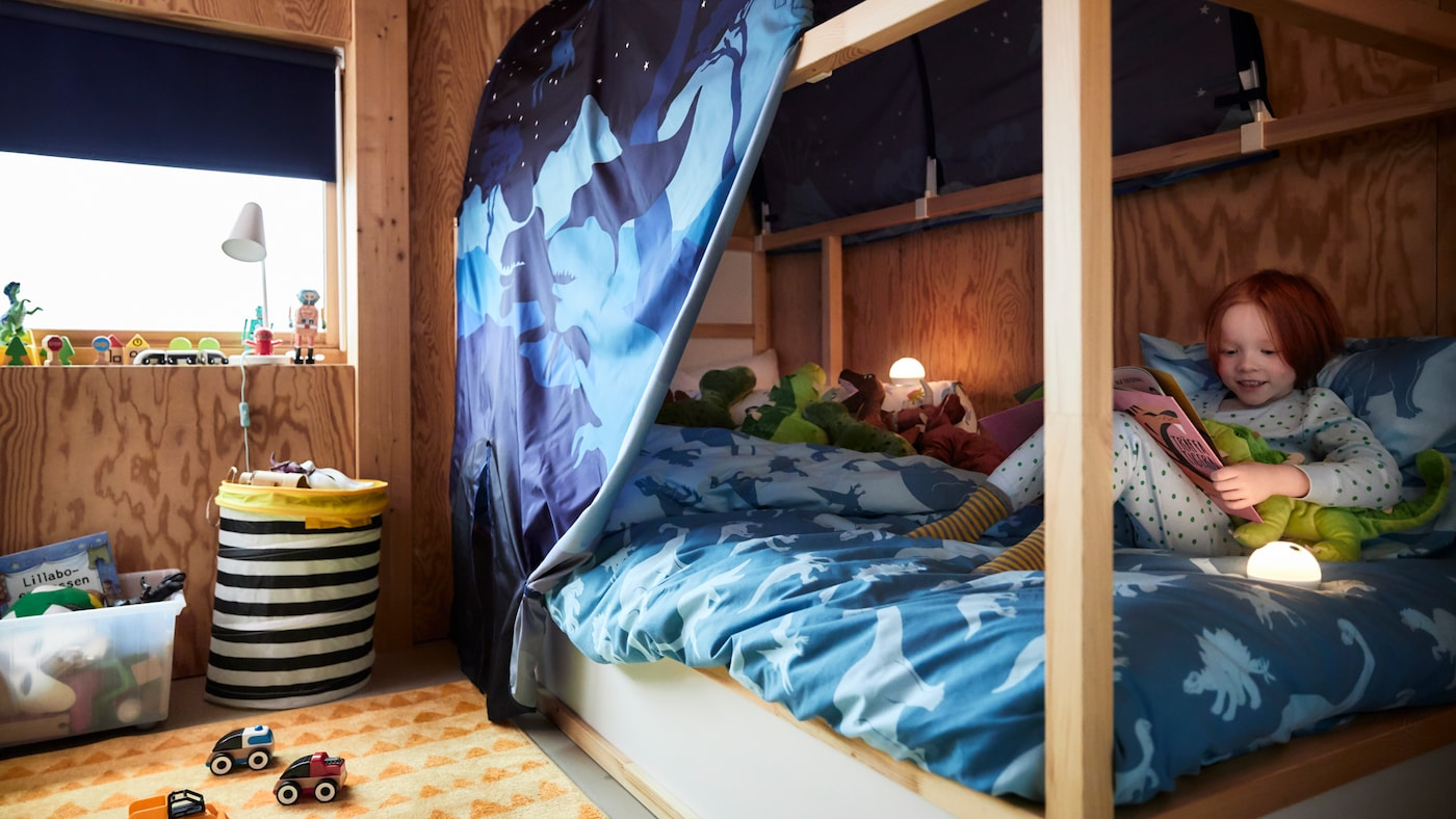 Un lit réversible KURA blanc dans une chambre d'enfant avec une tente et une housse de couette bleues à motifs dinosaures, un enfant assis dessus.