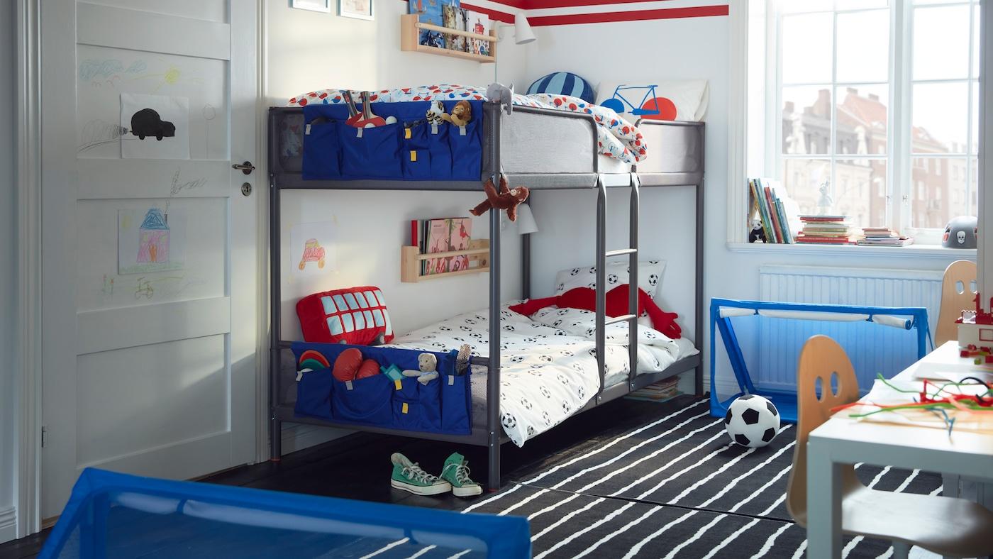 Un lit superposé TUFFING dans une chambre d'enfants, avec un ballon de football et deux mini buts par terre. Des poches de rangement bleues sont accrochées au pied de chaque couchage.