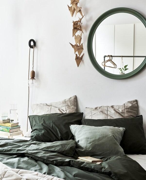 Un llit amb roba de llit verda i un mirall verd a la paret.