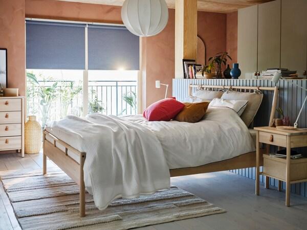 Un llit BJÖRKSNÄS en una habitació amb les parets folrades de fusta mentre la llum entra per la finestra de darrere.