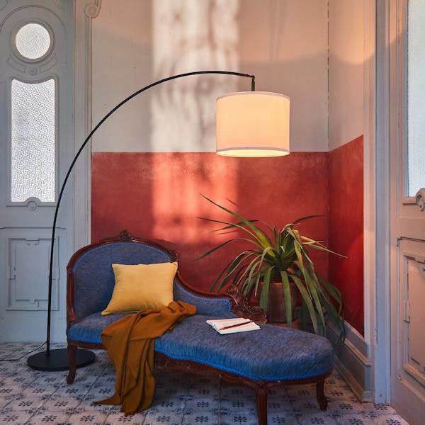 Un llum de peu SKAFTET amb base arquejada i pantalla blanca proporciona il·luminació des de dalt per a un divan situat en un racó.