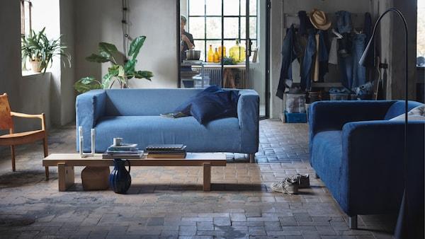 Un loft de style industriel avec sur un sol en pierre beige une table basse rectangulaire longue en bois avec autour deux KLIPPAN avec une housse en jean.