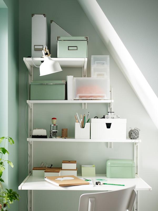 Un lugar de trabajo ordenado bajo un techo abuhardillado que se ha realizado utilizando estantes de almacenaje de pared de IKEA de anchos diferentes.