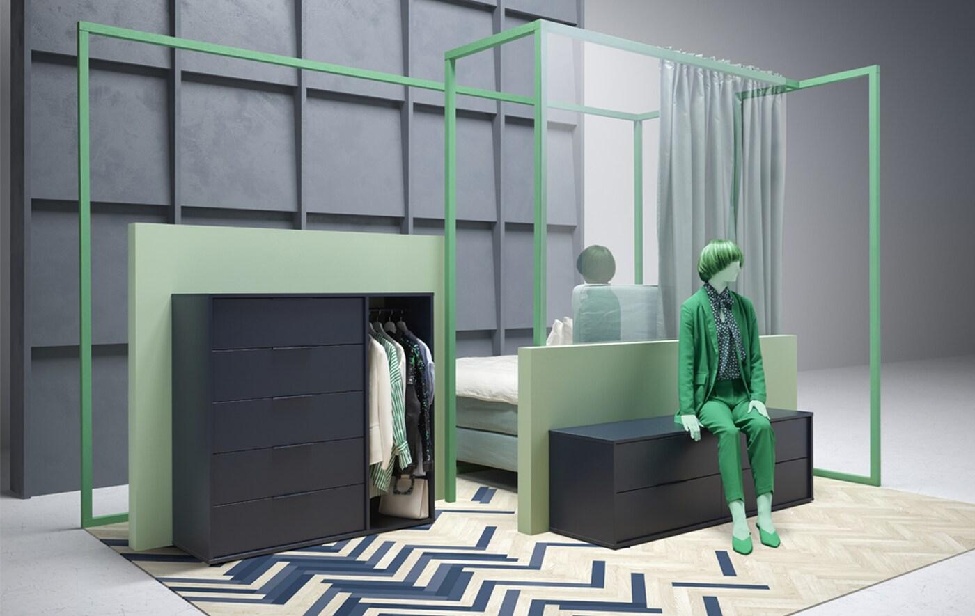 Un mannequin vêtu de vert assis sur une commode basse, à côté d'une commode plus haute avec des tiroirs et des vêtements qui y sont suspendus.