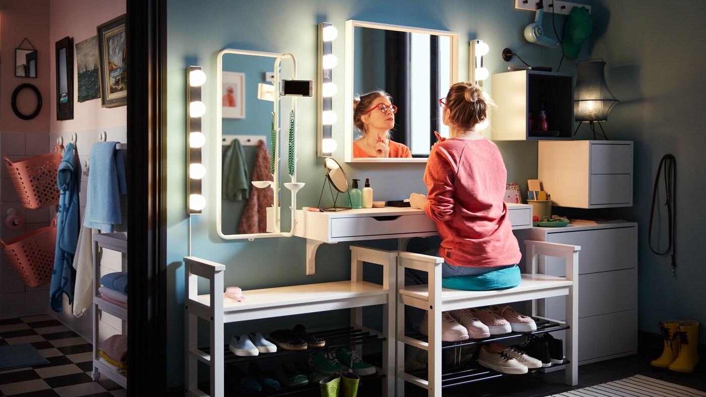 Un meuble pour lavabo légèrement tourné avec une femme qui applique du maquillage, assise sur un banc range-chaussures avec une étagère murale, de l'éclairage et des miroirs.