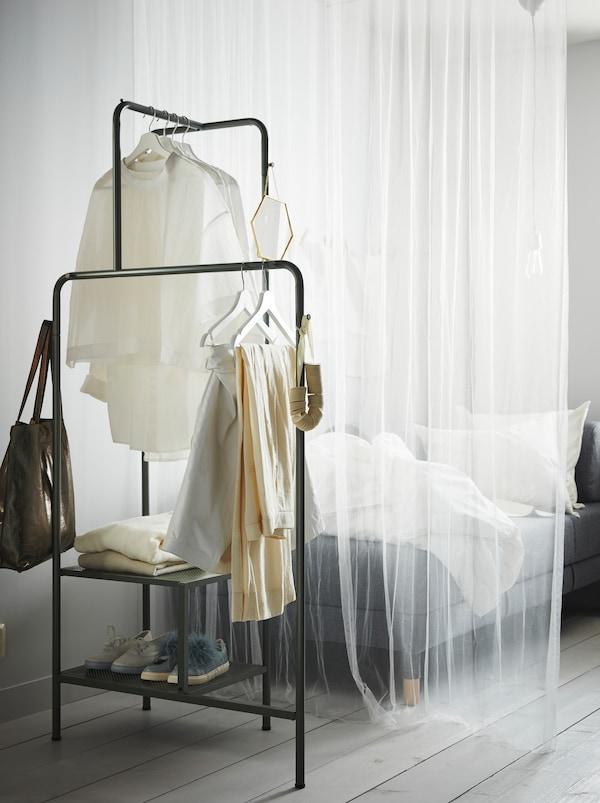 Un mince rideau blanc sépare un canapé d'un portant NIKKEBY gris-vert où sont posés chaussures, vêtements etaccessoires.
